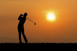Silhouette of golfer against sunset